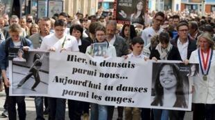 """Manifestantes de Caudry, no norte da França, carregam faixa em homenagem à professora de dança e ginástica Aurélie Châtelain com a inscrição: """"Ontem você dançava entre nós. Hoje você dança entre os anjos""""."""