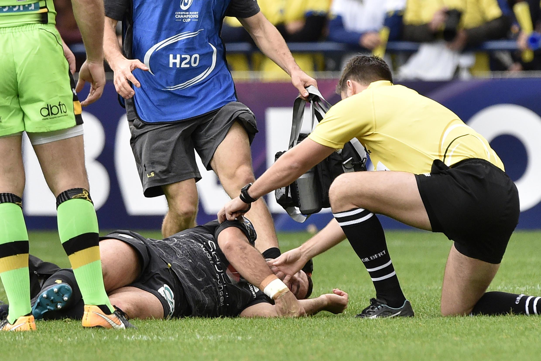 Árbitro ajuda jogador do ASM Clermont Auvergne com suspeita de concussão cerebral durante partida do Campeonato Europeu de Rugby contra os Northampton Saints, outubro de 2017