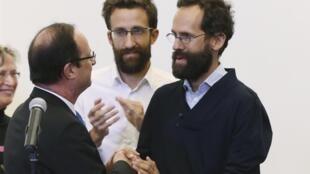 Deux des ex-otages Tanguy (d) et Cyril Alain-Fournier (c), accueillis par le président François Hollande, à l'aéroport d'Orly, le 20 avril 2013.