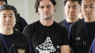 """Hadziahmetovic, uno de los presumibles cerebros de los """"Pink Panther"""", escoltado por guardias de la policía japonesa, este sábado, en Madrid."""
