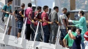 Des migrants débarquent d'un navire des garde-côtes italiens sur le port de Palerme, en Sicile, le 20 août 2015.