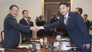 Trưởng đoàn Hàn Quốc, thứ trưởng bộ Giao Thông Kim Jeong-ryeol (P) bắt tay đồng nhiệm Bắc Triều Tiên Kim Yun Hyok, trong cuộc gặp tại Bàn Môn Điếm, ngày 26/06/2018