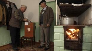 Les Biélorusses se rendent aux urnes, dimanche 11 octobre, pour exprimer leur vote lors des élections présidentielles de 2015. Ici, un homme dépose son bulletin dans l'urne portable, dans le village de Danilovich, au sud-ouest de Minsk.