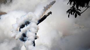 """Un manifestante devuelve una granada de gas lacrimógeno a la policía antidisturbios durante la llamada """"madre de todas las marchas"""" contra el presidente de Venezuela, Nicolás Maduro, en Caracas, Venezuela, el 19 de abril de 2017."""