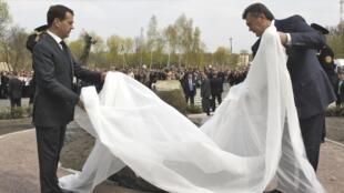 Le président russe Dmitri Medvedev (g) et son homologue ukrainien Viktor Yanukovich lèvent le voile d'un nouveau mémorial aux liquidateurs de Tchernobyl, le 26 avril 2011 à Tchernobyl.