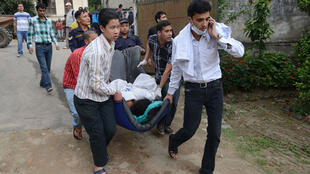 Des passants viennent en aide aux victimes du séisme qui a frappé la ville de Katmandou au Népal, le 25 avril 2015.