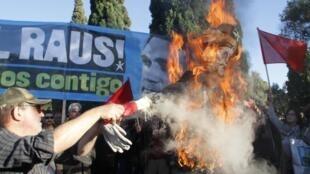 Manifestantes queman la imagen de la canciller alemana Angela Merkel en Lisboa, el 12 de noviembre de 2012.