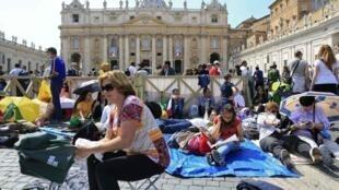 """Turistas """"acampados"""" na praça São Pedro, no Vaticano, aguardam para assistir a canonização, neste domingo, de João Paulo II e João XXIII."""