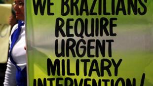 """""""Nós brasileiros pedimos intervenção militar urgente"""", diz cartaz em inglês exibido em manifestação de apoio a caminhoneiros em São Paulo, no dia 28 de maio."""