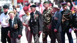 Arrivée de vétérans escortés par des soldats sur la plage de Ouistreham, juste avant la cérémonie le 6 juin 2014.