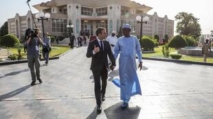 French President Emmanuel Macron and Chadian President Idriss Deby walk hand in hand at the presidential palace in N'Djamena on 23 December 2018.