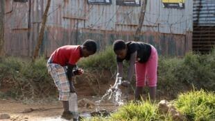 Deux enfants sud-africains jouent avec de l'eau sous des affiches électorales à Bekkersdal, township à l'est de Johannesburg, mai 2014 (photo d'illustration).