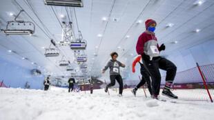 """Participantes de la """"DXB Snow Run"""", una carrera de tres kilómetros que tiene lugar a una temperatura de -4 grados centígrados en el centro de esquí de Dubai, en el emirato del golfo, el 14 de agosto de 2020"""