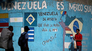 Venezolanos transitan delante de un mural que hace referencia al Mercosur, Caracas, este 1 de Diciembre de 2016.