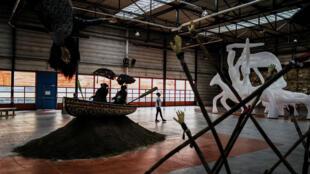 Une personne passe devant l'installation de l'artiste sud-africaine Simphiwe Ndzube le 16 septembre 2019 sur un ancien site de production de Fagor-Brandt, 2 jours avant l'ouverture de la 15e Biennale d'art contemporain de Lyon.