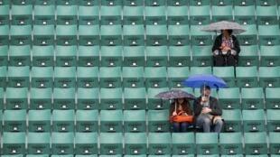 Algunos espectadores esperan a que la lluvia amaine en Roland Garros, este 4 de junio de 2014.
