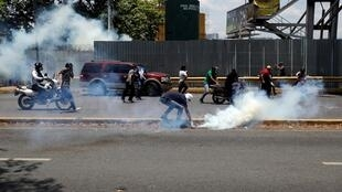 """Wafuasi wa upinzani wakikabiliana na vikosi vya usalama va Venezuela katika kambi ya kijeshi ya """"La Carlota"""" Caracas."""