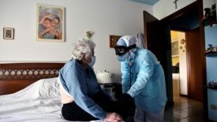 Un médecin italien rendant visite à une personne âgée souffrant du Covid-19, le 16 avril, à Bergame, devenue ville symbole des décès liés au virus.