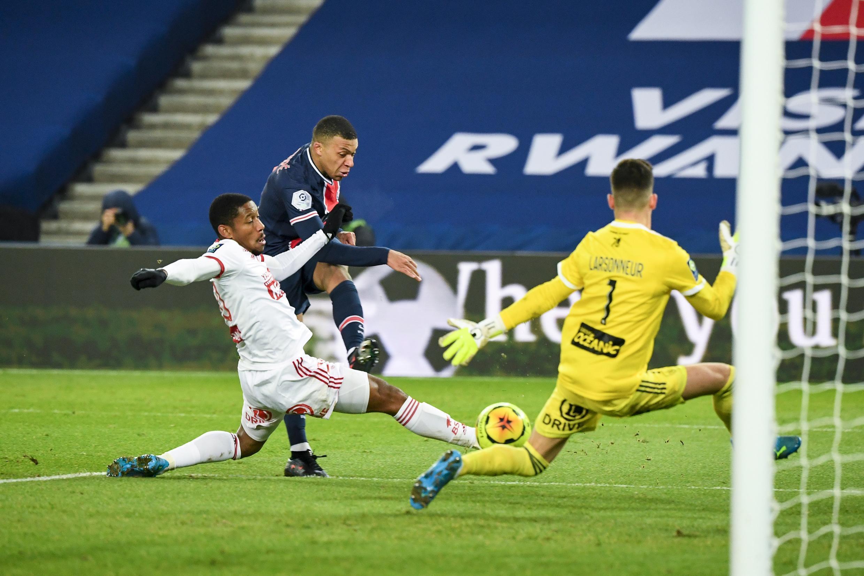 Kylian Mbappé (C), del PSG, remata sobre la portería del Brest, en partido de la liga francesa jugado el 9 de enero de 2021 en París