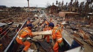 Các nhân viên cứu hộ dọn dẹp một khu vực bị đốt cháy sau bạo động giữa người Hồi giáo và Phật giáo tại Sittwe, Miến Điện ngày 16/06/2012.