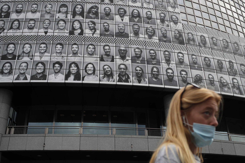 Pedestre passa diante de fotos de profissionais da saúde que trabalharam durante a epidemia de coronavírus na França. A homenagem é exibida na Ópera de Bastilha, no leste de Paris.