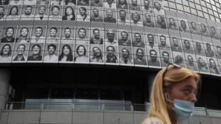 Une femme masquée passe devant l'opéra de Paris  à Bastille décoré des visages des soignants qui on travaillé pendant la pandémie le 10 juillet 2020.
