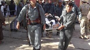 Des policiers afghans transportent un blessé après l'attentat-suicide dans la mosquée Eid Gah. Maymana, le 26 octobre.