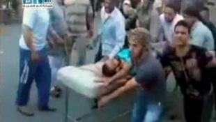 Un manifestant bléssé par les forces de sécurité entrain d'être acheminé à l'hopital  Al Badra de Hama en Syrie, le 31 juillet 2011.
