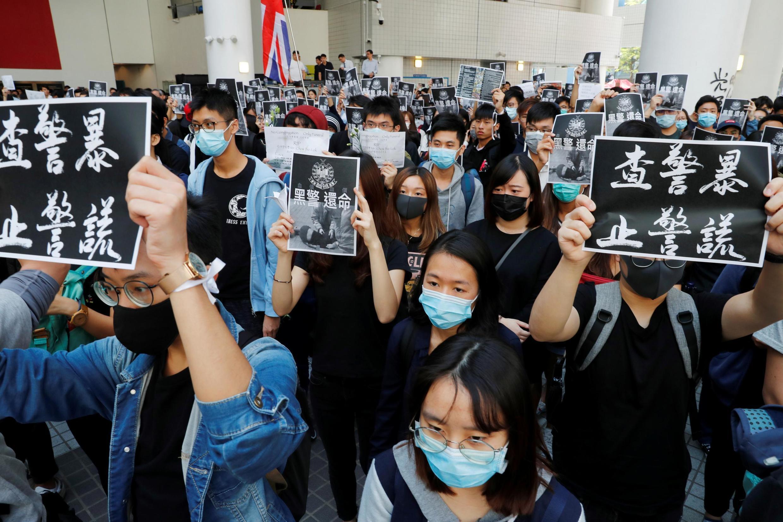 Estudantes assistem a uma cerimônia de homenagem a Chow Tsz-lok, 22 anos, um estudante universitário falecido durante protesto.