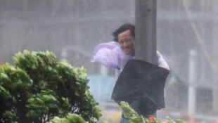 A Hong Kong, devant la force du vent, cet homme s'accroche à un lampadaire, le 23 août 2017.
