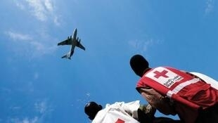 ICRC staff in Leer, Unity State, South Sudan watch the air drop of goods for beleaguered civilians on the ground