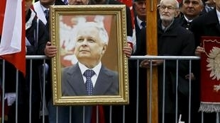 Un homme tenant un portrait de l'ex-président Lech Kaczynski, le 10 avril 2016 à Varsovie, lors de la cérémonie en hommage aux victimes du crash de Smolensk, qui a coûté la vie en 2010 au président polonais et 95 autres personnes.