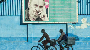 In this file photo men ride bicycles near a poster of the late Cuban leader Fidel Castro in Havana, on July 12, 2021