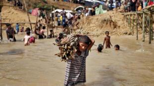 Un jeune réfugié de Birmanie transporte du bois dans l'eau boueuse d'un camp de Cox's Bazar, de l'autre côté de la frontière, au Bangladesh, le 22 septembre 2017.