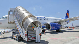 An Israeli worker in full hazmat suit sprays disinfectant on the stairs of an Israir airplane at Ben Gurion airport near Israel's Tel Aviv, in this file picture taken on June 14, 2020, amid the Covid-19 pandemic