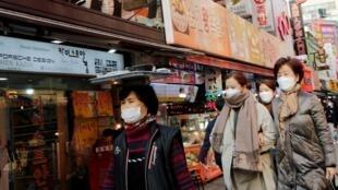 Mulheres usando máscaras como medida preventiva contra o coronavírus caminham em um mercado tradicional em Seul, Coreia do Sul, 20 de fevereiro de 2020.