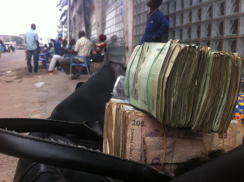 Des liasses de billets de francs congolais sur le sac d'une femme, à Kinshasa. (Image d'illustration)