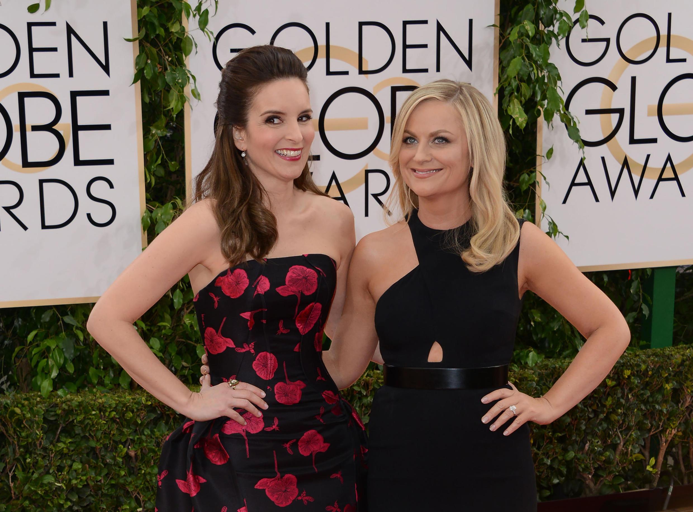 Las humoristas Tina Fey (izq.) y Amy Poehler (der.) vuelven a presentar los Globos de Oro una vez más en 2021, pero esta vez no estarán juntas sino en costas opuestas.