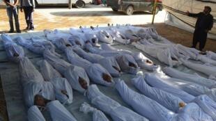 Des activistes syriens inspectent des corps de civils tués, selon eux, par des agents chimiques, le 21 août, dans la banlieue de Damas.