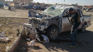 A policeman inspects a damaged vehicle at the site of a bomb attack in Ramadi