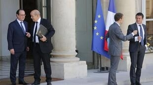 French President Francois Hollande (L) escorts Defence Minister Jean-Yves Le Drian as Economy Minister Emmanuel Macron (2ndR) and Prime Minister Manuel Valls (R) speak to each other after final cabinet meeting of season. Paris, July 31, 2015