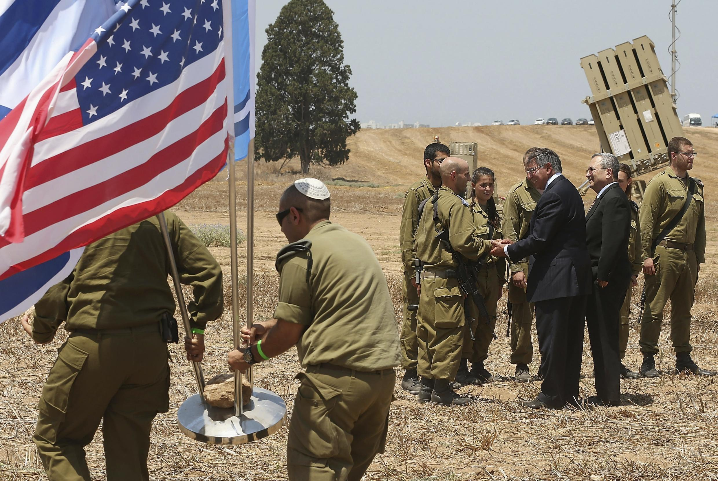 US Defense Secretary Leon Panetta and Israeli Defense Minister Ehud Barak greet Israeli soldiers after a joint news conference during a visit to the Iron Dome defense system launch site in Ashkelon