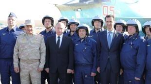 Tổng thống Nga Vladimir Putin, bộ trưởng Quốc Phòng Sergei Shoigu (trái, hàng trên) và tổng thống Syria Bashar al-Assad (thứ hai bên phải, hàng trên) tại cơ sở không quân  Hmeymim tại tỉnh Latakia, Syria, ngày 11/12/2017.