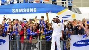 O atleta de salto triplo britânico Phillips Idowu carrega a tocha olímpica em Nowham, em Londres, neste sábado.