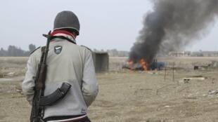 Un combattant sunnite observe une voiture de police en train de brûler, à Ramadi, le 2 janvier 2014.