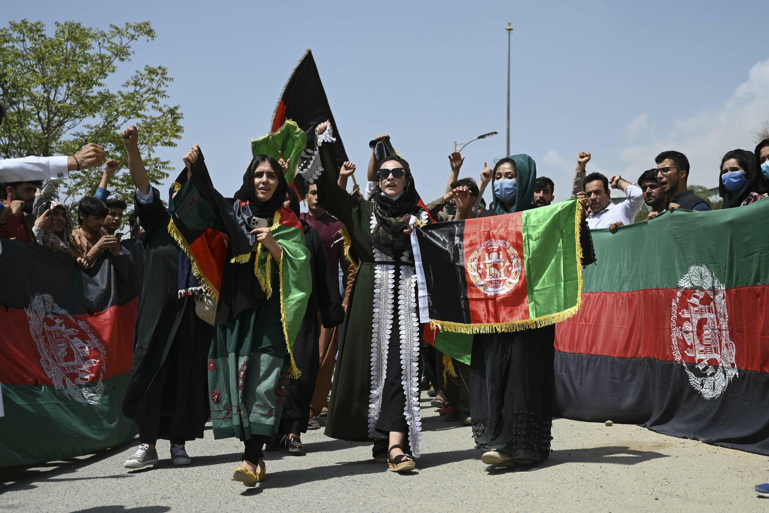 A small group of Afghans celebrates Independence Day by unfurling the national flag just days after the Taliban's conquest of the country