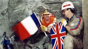 1er décembre 1990. Les ouvriers Philippe Cozette (D) de France et Graham Fagg d'Angleterre (G) se serrent la main tout en tenant leur drapeau national respectif, lors de la percée finale du tunnel sous la Manche, au point de jonction des deux tunneliers.
