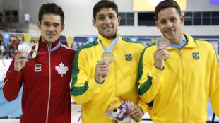 Da esquerda para direita: Richard Funk, do Canadá (prata), Thiago Simon (ouro) e Thiago Pereira (bronze), ambos do Brasil, comemoram vitória nos 200 metros peito nos Jogos Pan-Americanos, nesta quarta-feira (15), em Toronto.