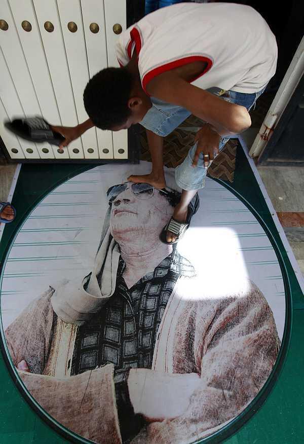 Un niño libio da zapatazos a un retrato de Kadafi; el 16 de julio de 2011 en Misrata.