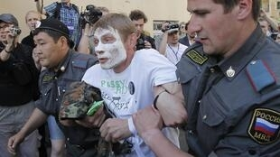 Российские полицейские задерживают участника акции в поддержку девушек группы Pussy Riot в Москве 20 июня 2012 г.